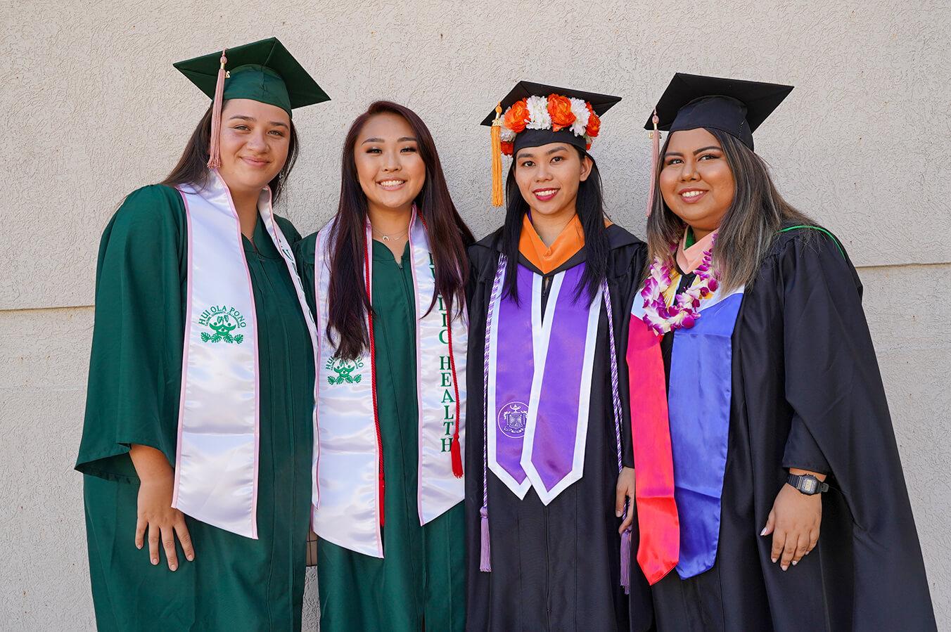 Four UH Manoa students in their graduation regalia