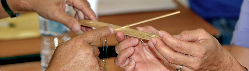 photo of teachers conducting an experiment with rulers, paper clips and chopsticks