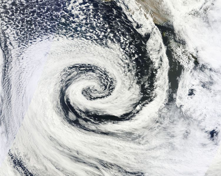 <p><strong>Fig. 3.9.</strong> (<strong>B</strong>) A low-pressure system spiraling clockwise over Australia in the Southern Hemisphere.</p>