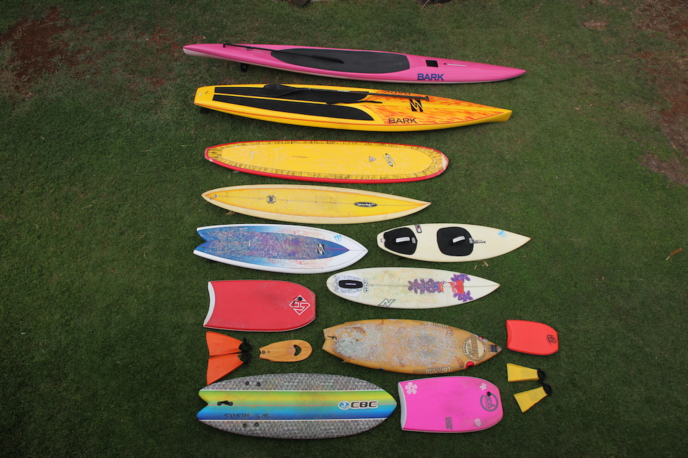 """<p><strong>SF Fig. 4.2.</strong> (<strong>B</strong>) A versatile surf quiver can include many types of crafts, for example the quiver shown here includes a 14' prone paddleboard, a 12'6"""" standup paddleboard and paddle, a 9' long board, a 8' gun surfboard, a 5'8"""" tow surfboard with straps, a 5'8"""" fish surfboard, s 5'9"""" shortboard, s 3'6"""" body board, s 6' retro fish surfboard, s 1.5' mini body board, orange surf fins, s wooden hand plane for body surfing, s 6'5"""" foam fish surfboard, s 3'1"""" bodyboard, and yellow surf fins.</p>"""