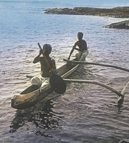 Two boys paddling an outrigger canoe with link to image source
