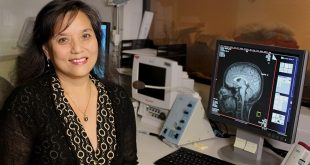 John A. Burns School of Medicine's Linda Chang in front of a brain scan of an 8-year-old child