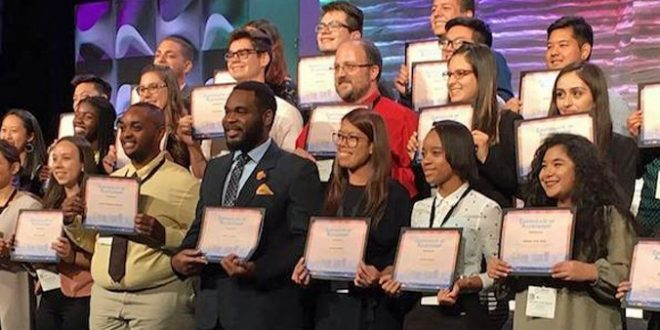 Michael Fernandez and Jovikka Antallan on stage with other conference award winners.