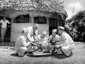 Photo of shop owner demonstrating how to pound poi to soldiers