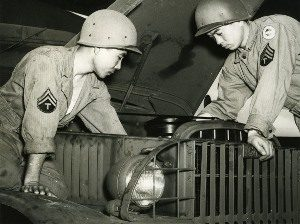 Photo of two soldiers in the 100th Infantry Battalion repairing a truck during training.