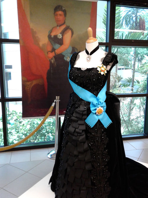 Queen Liliʻuokalani's dress in front of a painting of her in the dress