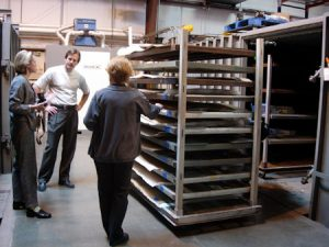 Workers standing next to a rack of materials