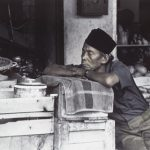 Photograph of Indonesian man in shop by Penny Kaiman-Rayner