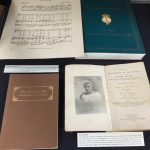 Books and sheet music on the left side of the Queen Lili'uokalani display