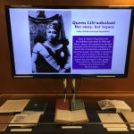 A monitor displaying information about Queen Liliuokalani and a display of various books beneath