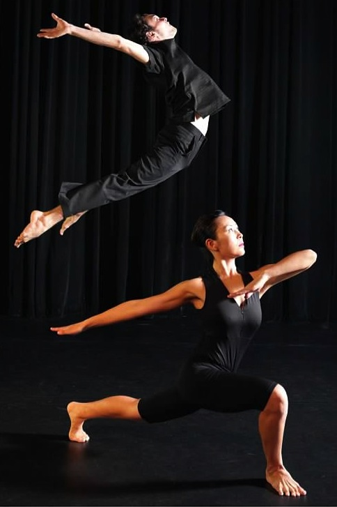 Photo of two dancers; one lunges the other jumps in the air with arched back