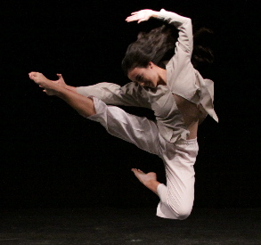 Performer leaping in the air with right leg outstretched and left leg tucked in