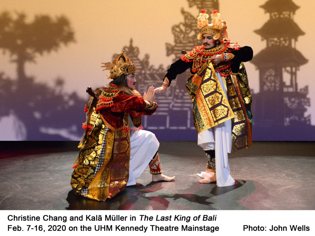 """Two actors in golden Balinese garb, one kneeling to the other, in front of shadow screen showing trees and pagoda. Christine Chang and Kala Muller in """"The Last King of Bali"""" Feb. 7-16, 2020 on the UHM Kennedy Theatre mainstage. Photo by John Wells"""