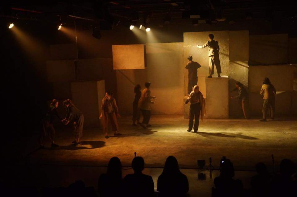 Actors spread out over a dimly lit space, two standing on blocks, and four in the back touching the rear wall