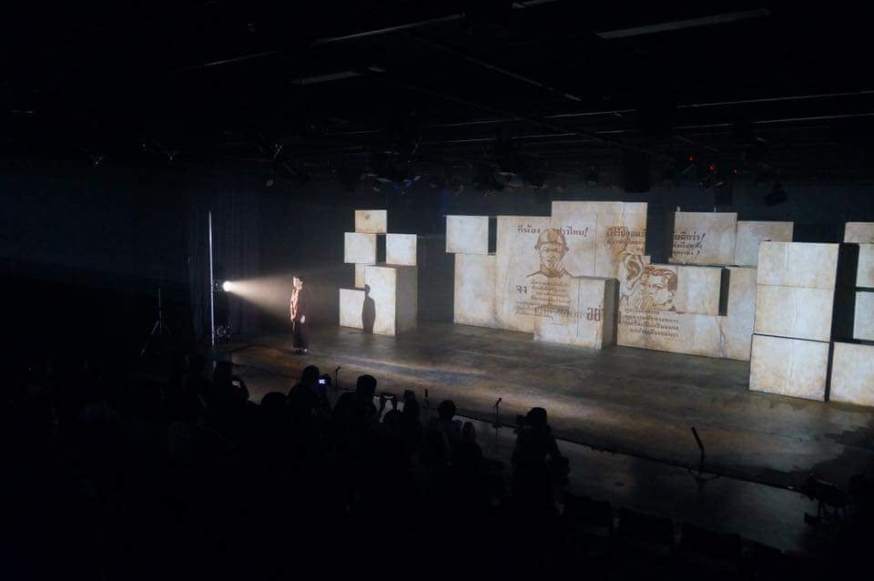 An actor stands to the left looking straight out to the audience with a light focused on his head and upper body. Behind him, drawings and text are projected onto blocks.