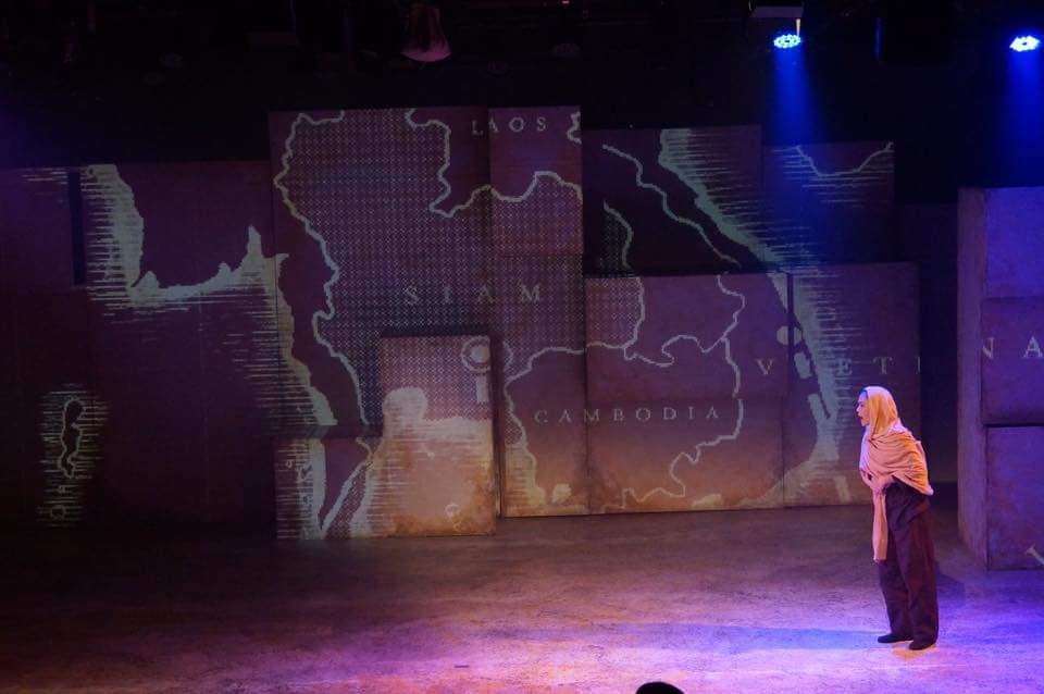 A female performer in a head scarf stands to the right, in front of a projection of a map of the region of Southeast Asia centered around Thailand, which labeled here as Siam