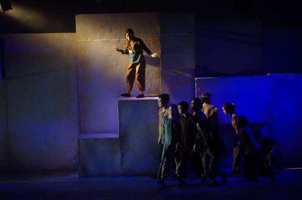 A group of performers moving across the stage in dim blue and yellow lighting, with one actor above the rest standing on a tall block