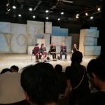 """Parichat Jungwiwattanaporn and others sitting on stage answering audience questions, in front of a projection of the show title, """"The Voyage,"""" on the blocks behind them"""