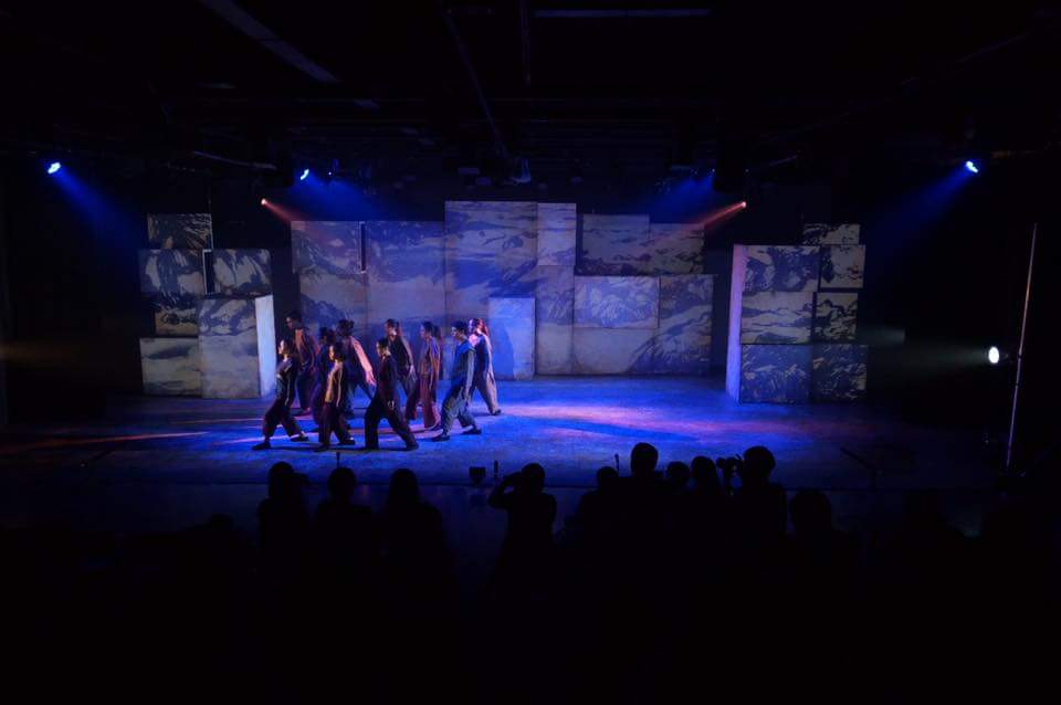 A cluster of performers moving in unison across the stage in blue light with images of mountains projected onto stacks of blocks behind them