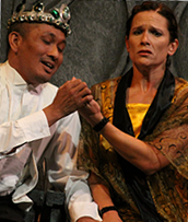 Two performers; one wears a crown and is holding/looking at the others hand