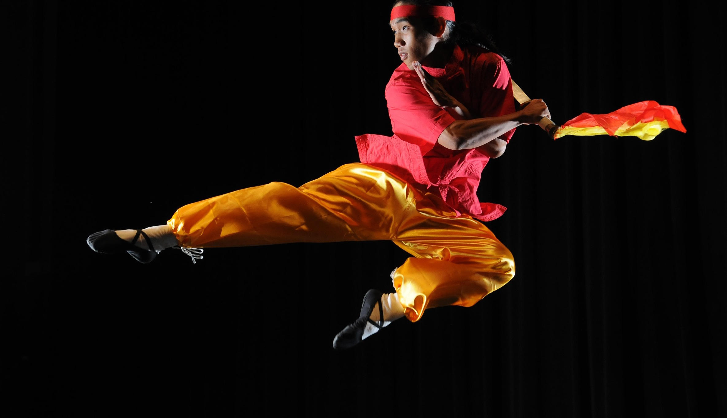 Photo of performer jumping in air with one leg outstretched, the other bent