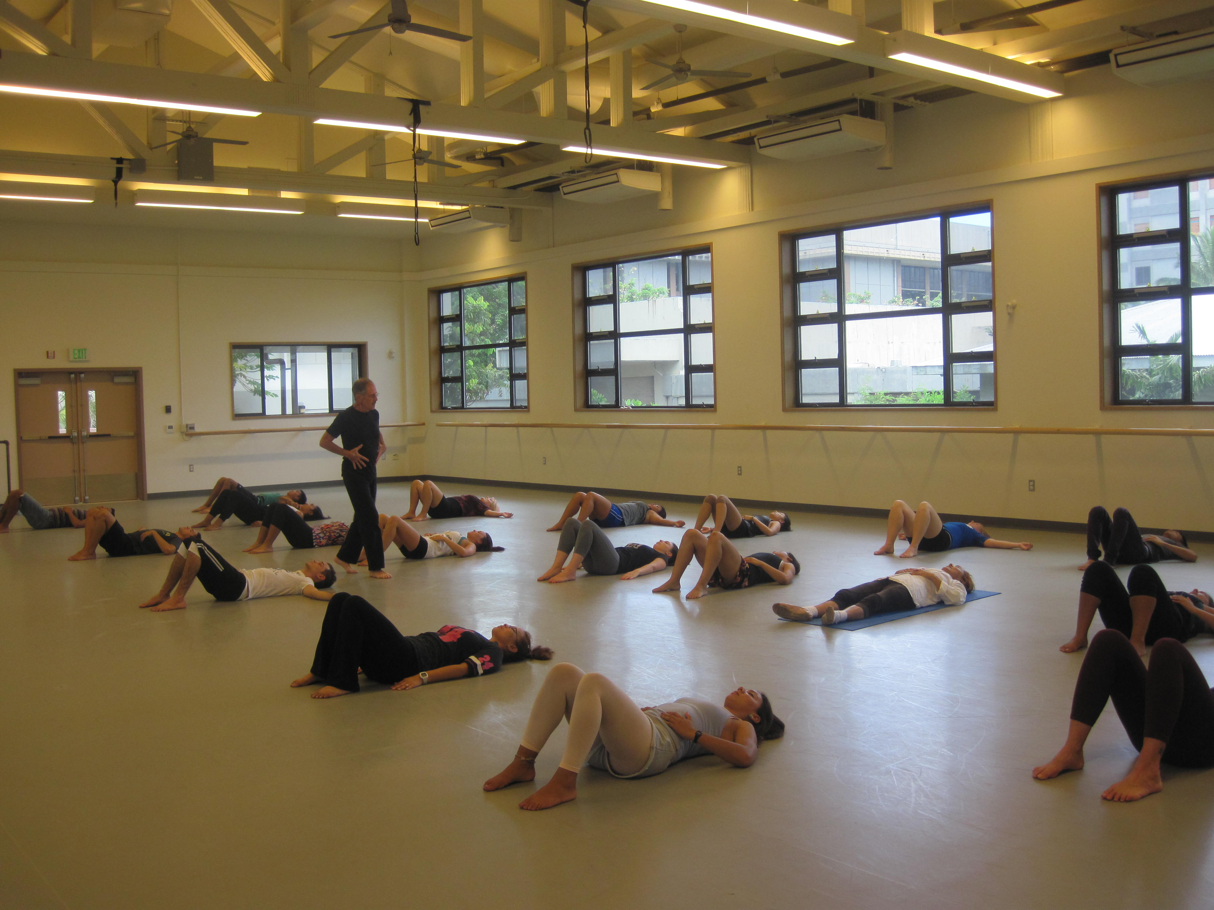Students in dance classroom lying on floor with instructor walking around