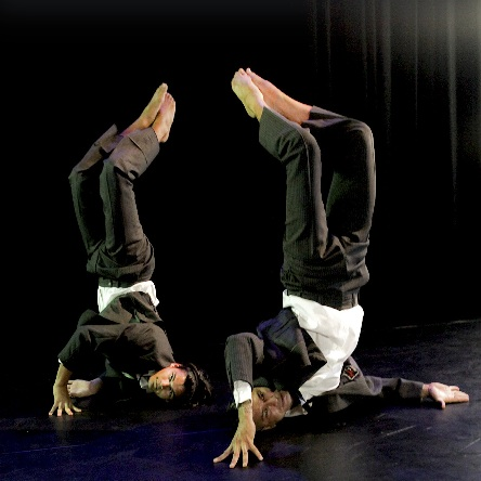 Two dancers with shoulders on the ground and feet in the air point towards one another