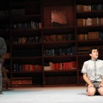 Photo from production of The Giver; two performers both in gray with bookshelf set in the background