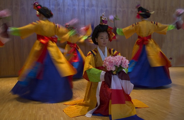 Dancers in bright costuming; center dancer squatting holding flowers; more dancers circle around