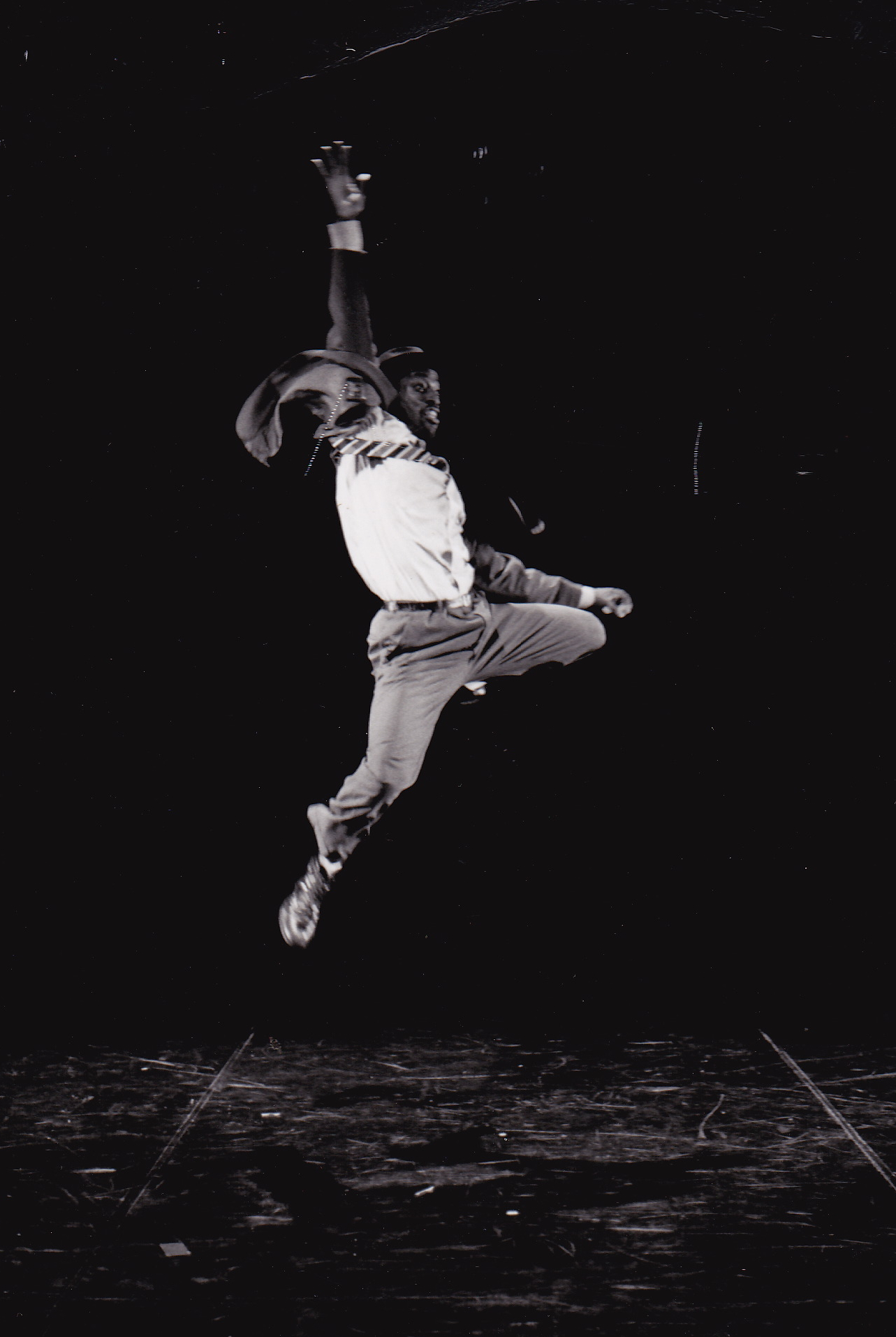 Dancer jumping in the air with one arm outstretched