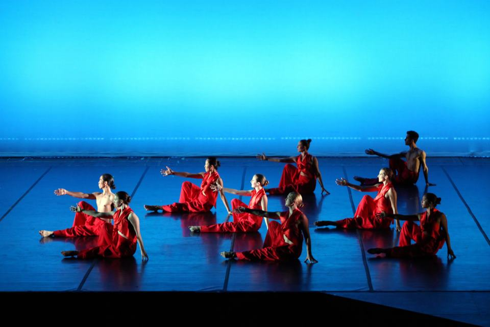 Photo from dance concert with dancers sitting on ground reaching out in front of them