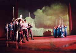 Group of performers in two separate clumps holding tall rods
