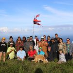 EA Hawaiʻi Field School students, faculty and staff pose for a picture by a Hawaiian flag fanning in the wind at Kahikinui