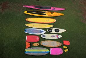 """<p><strong>SF Fig. 4.2.</strong> (<strong>B</strong>) A versatile surf quiver can include many types of crafts, for example the quiver shown here includes a 14' prone paddleboard, a 12'6"""" standup paddleboard and paddle, a 9' long board, a 8' gun surfboard, a 5'8"""" tow surfboard with straps, a 5'8"""" fish surfboard, s 5'9"""" shortboard, s 3'6"""" body board, s 6' retro fish surfboard, s 1.5' mini body board, orange surf fins, s wooden hand plane for body surfing, s 6'5"""" foam fish surfboard, s 3'1"""" bodyboard, and yellow surf fins.</p><br />"""