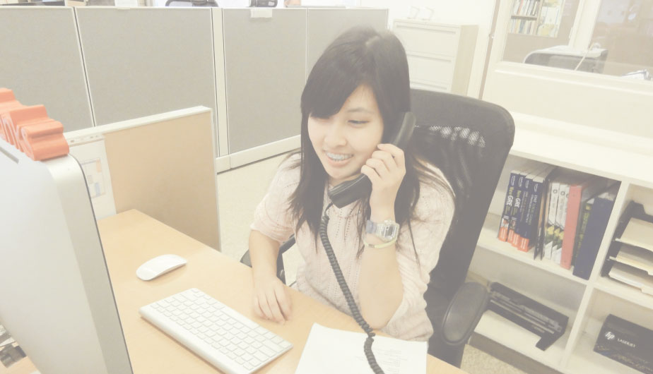 Photo of student employee smiling and sitting in a cubicle answering the phone