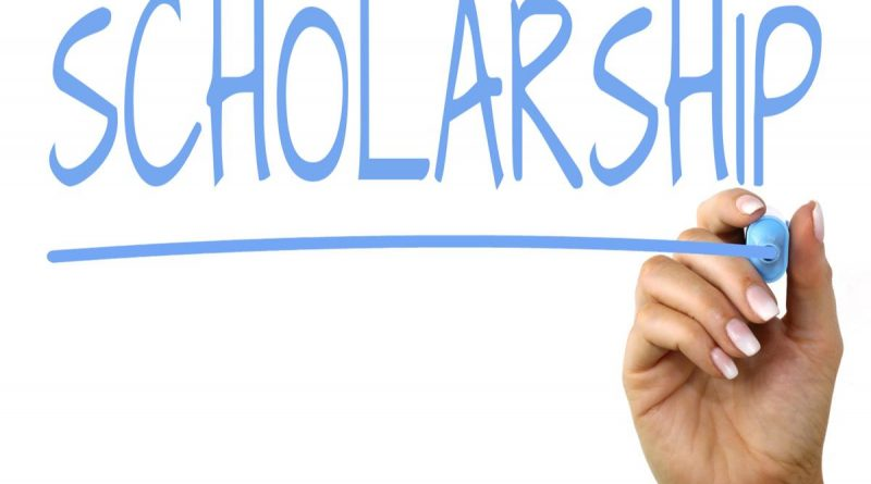 Hand Using Pen to Write the Word Scholarship