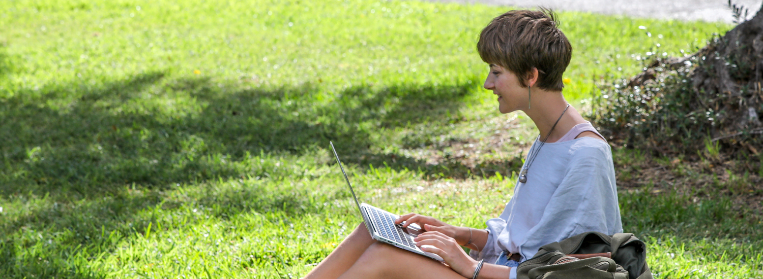 A student sitting on the grass looking at a laptop