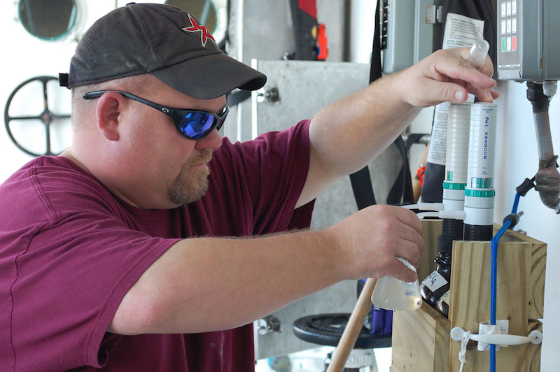 <p><strong>Fig. 2.6.</strong> (<strong>A</strong>) A scientist adds chemicals to a water sample from the Gulf of Mexico aboard the National Oceanic and Atmospheric (NOAA) Ship <em>Pisces</em>. The sample will be analyzed to determine levels of dissolved oxygen.</p>