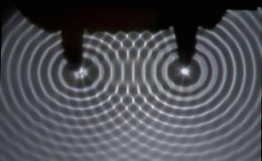 <p><strong>Fig. 4.11.</strong> Two sets of generated waves in a ripple tank. Notice the patterns of interference where wave sets meet.</p><br />