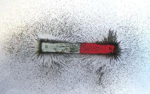 <p><strong>SF Fig. 7.5.</strong> The orientation of iron fillings makes the magnetic field lines around a bar magnet visible. Iron is a magnetic material that is either repelled or attracted to the two poles of the bar magnet.</p>