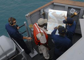 <p><strong>Fig. 8.2.</strong> US Navy officers navigate their warship into a foreign port with the aid of a local pilot and nautical chart.</p><br />