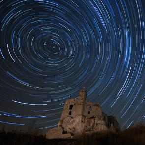 <p><strong>Fig. 8.6.</strong> (<strong>B</strong>) In the Northern Hemisphere, stars appear to rotate around the North Star throughout the night. This photo was taken at Mìrow castle in Poland.</p><br />