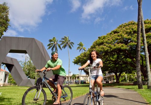 Two Students Riding Bikes On Campus