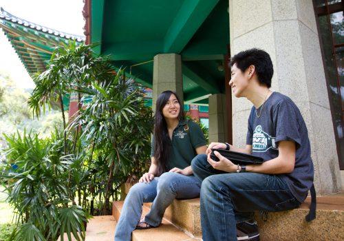 Students Sitting On Steps Of Korean Studies Building