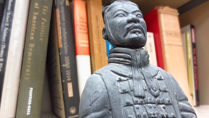 Emperor Qinshihuang's terracotta soldier replica in front of books