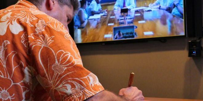 UH Mānoa Interim Chancellor David Lassner signing an agreement