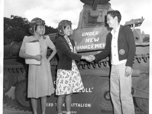 Students shaking hands in front of a tank