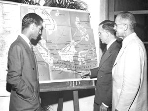 G. W. Fisher and Charles F. Loomis listen as James H. Shoemaker points to map of Netherlands (Dutch) East Indies at Report of 10th IPR Conference, Montague Hall, Punahou School, 6 Oct. 1947.