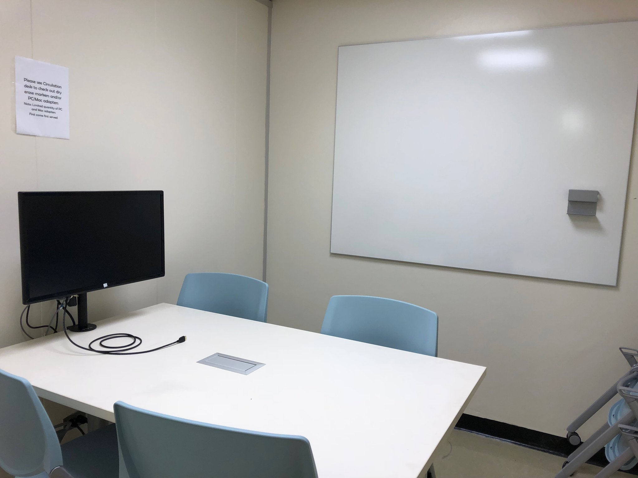 a group study room with 4 chairs, a table, monitor, and whiteboard