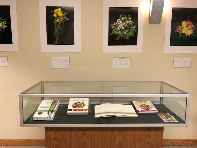 Display of pictures and books on floral arrangements